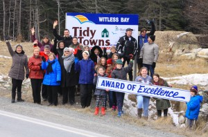 "Representatives from a good number of the groups who pitched in with our Tidy Towns bid are putting up the town's new ""Award of Excellence"" sign. The groups represented in the picture include Witless Bay's Town Council, its staff, our summer student workers, the O'Connor 50+ Club, the Puffin & Petrel Patrol, C-Paws-NL, the Our Lady Star of the Sea Parish, the BBBAA, the Community Enhancement Committee, the Heritage Committee, Adopt-A-Spot participants, St. Bernard's Elementary School, Mobile High School, the Girl Guides, and the town's businesses."